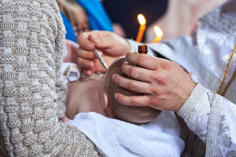 Das Sakrament der Taufe des Kindes in der orthodoxen Kirche, das Salben stockfotos