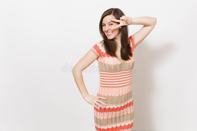 Das schöne junge brunette Mädchen im hellen beige und rosa kopierten Kleid lächelnd, hält Hand auf Taille und Showsieg stockfoto
