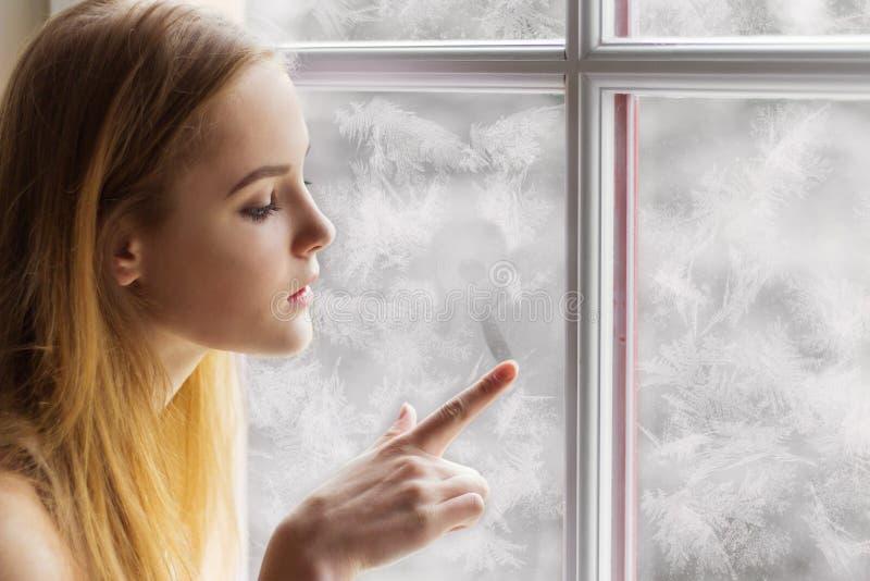 Das schöne junge Mädchen, das am Fenster Wintertag sitzt und zeichnet die Sonne auf dem gefrorenen Fenster lizenzfreie stockbilder