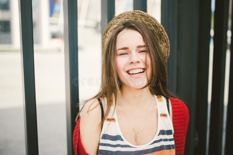Das schöne junge Mädchen, das lächelt, ist glücklich, glücklich in einem Hut, ein rotes Hemd über Stadt lizenzfreie stockbilder