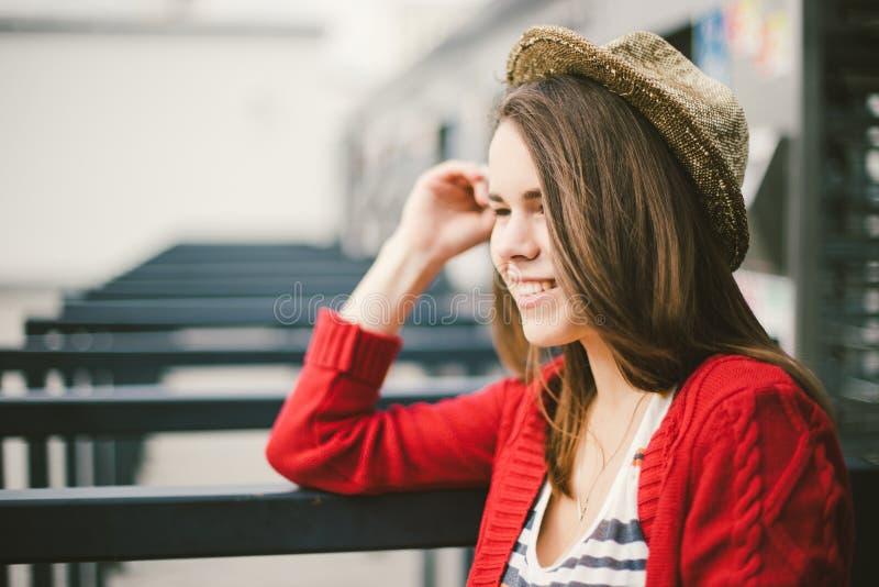Das schöne junge Mädchen, das lächelt, ist glücklich, glücklich in einem Hut, ein rotes Hemd über Stadt stockfotografie
