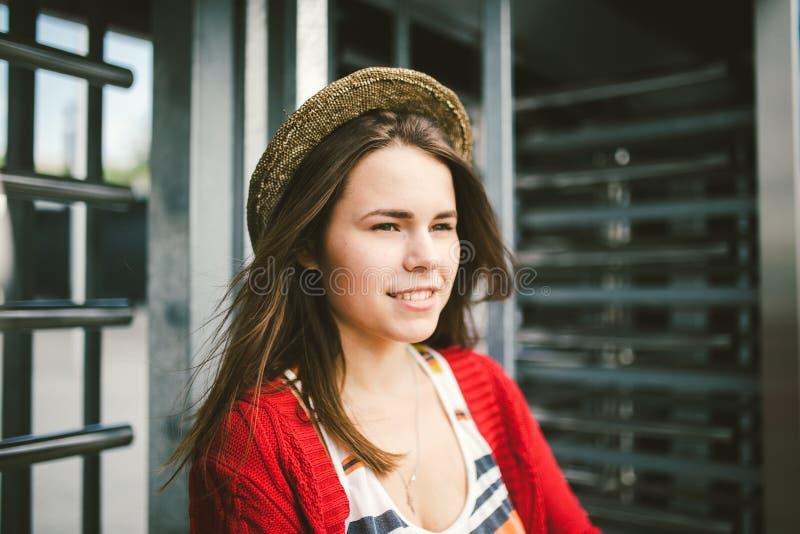 Das schöne junge Mädchen, das lächelt, ist glücklich, glücklich in einem Hut, ein rotes Hemd über Stadt lizenzfreie stockfotos