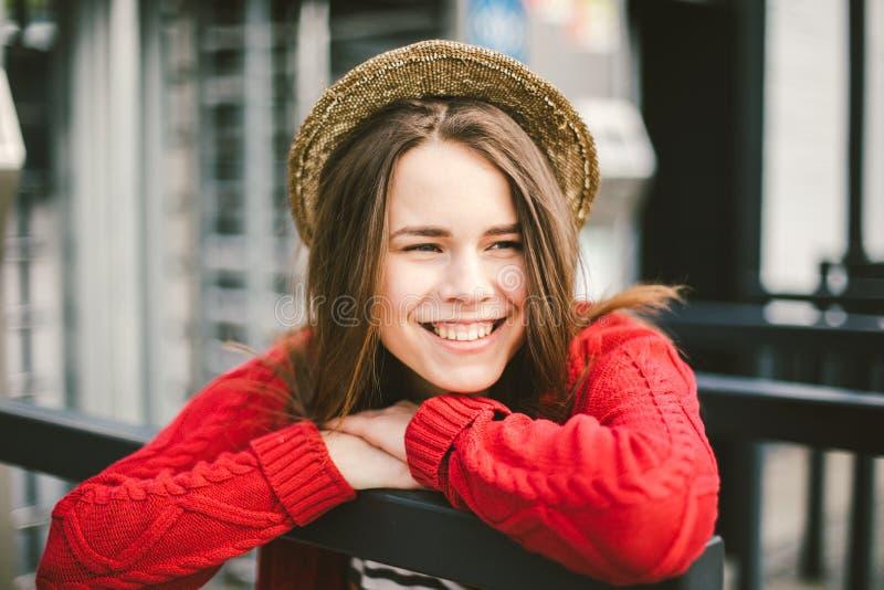 Das schöne junge Mädchen, das lächelt, ist glücklich, glücklich in einem Hut, ein rotes Hemd über Stadt lizenzfreies stockbild