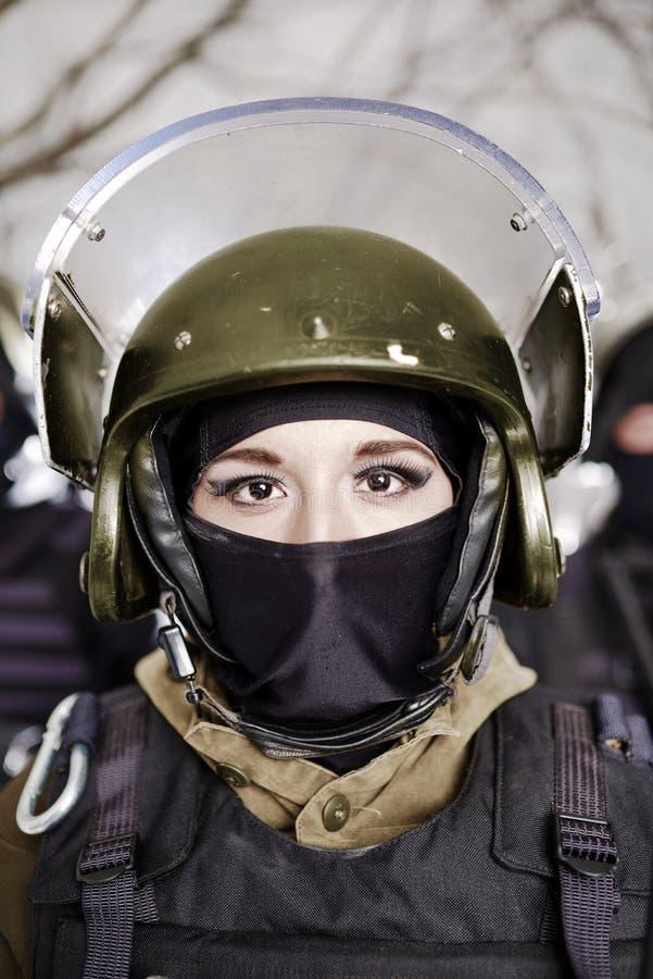 Das schöne junge Mädchen in einer Militäruniform und in einem Sturzhelm lizenzfreie stockfotografie