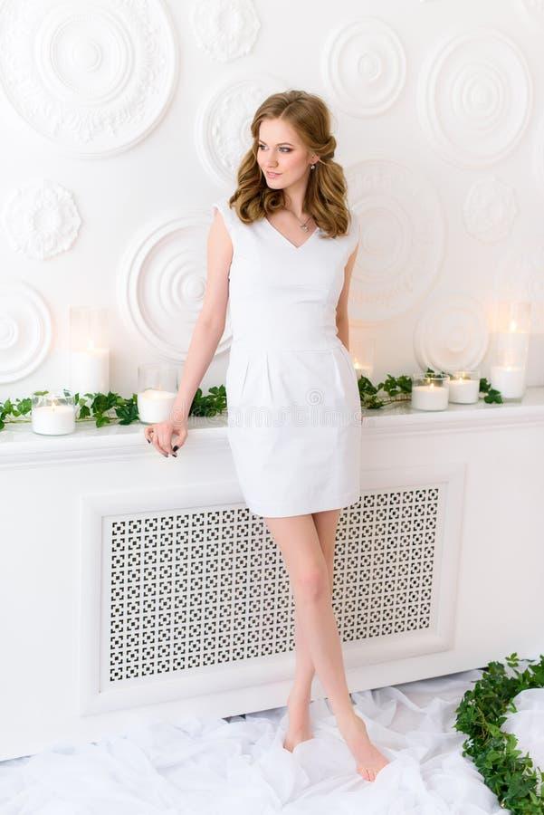 Das schöne junge Mädchen, das für ein Bild, das weiße Kleid aufeinander bezieht mit sauberen Wänden, lange schlanke Beine aufwirf stockbilder