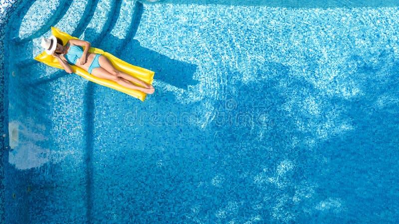 Das schöne junge Mädchen, das im Swimmingpool, Schwimmen auf aufblasbarer Matratze sich entspannt und hat Spaß im Wasser auf Fami lizenzfreie stockfotos