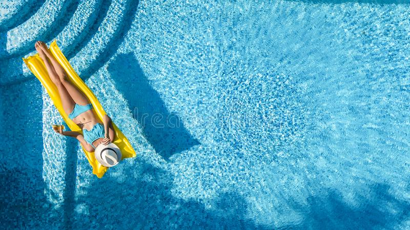 Das schöne junge Mädchen, das im Swimmingpool, Schwimmen auf aufblasbarer Matratze sich entspannt und hat Spaß im Wasser auf Fami lizenzfreies stockfoto