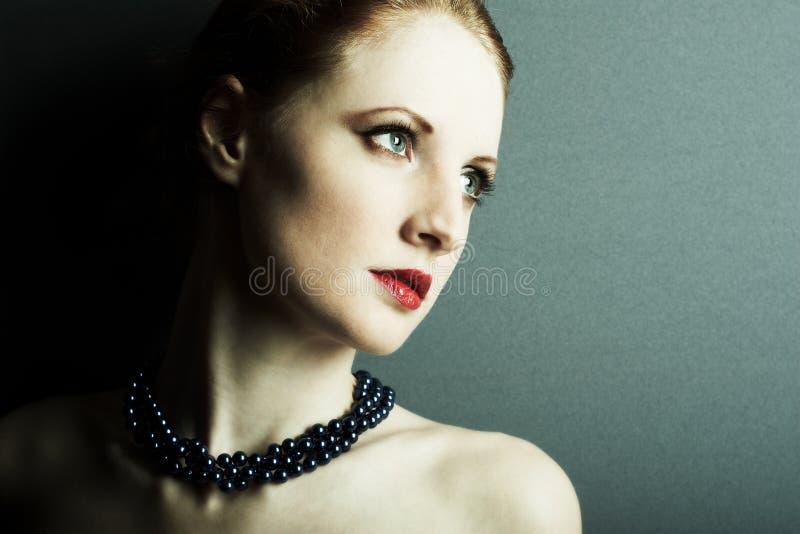 Das schöne junge Mädchen mit dunkelblaue Korne stockbilder