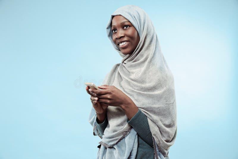 Das schöne junge schwarze moslemische Mädchen, das graues hijab, mit einem glücklichen Lächeln auf ihrem Gesicht trägt stockfoto