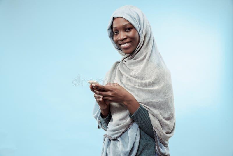 Das schöne junge schwarze moslemische Mädchen, das graues hijab, mit einem glücklichen Lächeln auf ihrem Gesicht trägt stockfotos