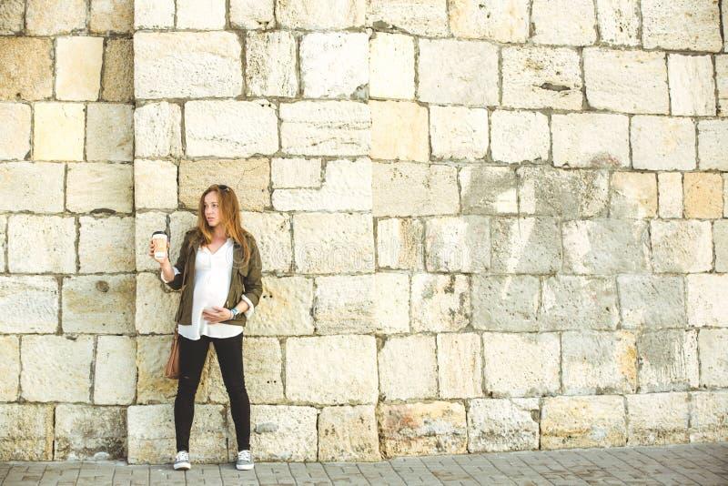Das schöne junge Trinken der schwangeren Frau nehmen Kaffee weg lizenzfreie stockfotografie