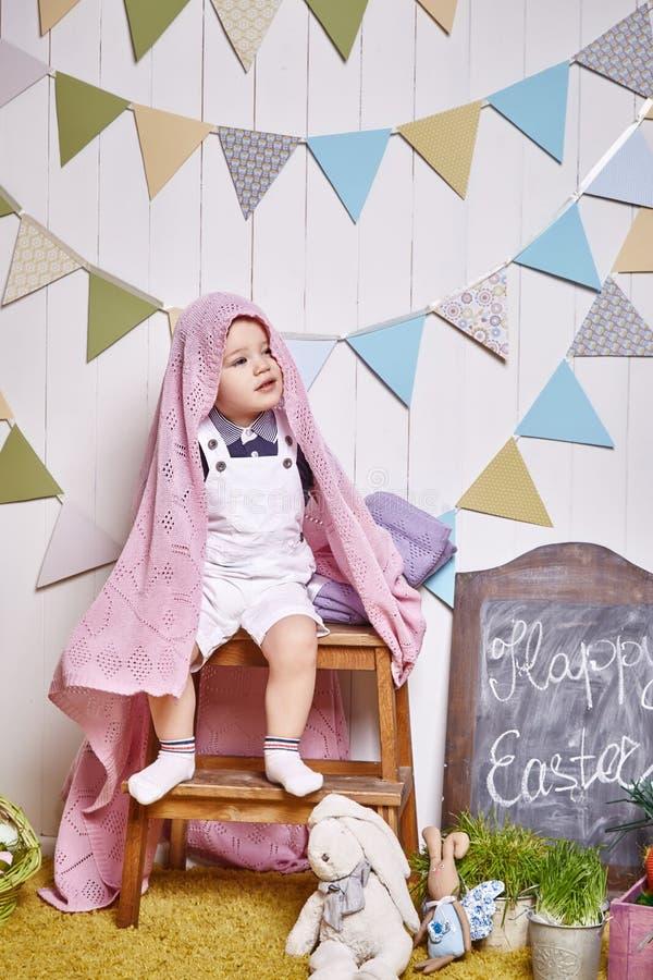 Das schöne kleine Baby, das auf einem Stuhl mit einem gestrickten umfassenden Ostern-Korb mit farbigen Eiern sitzt, heuen, Osterh stockfotografie