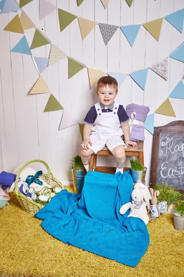 Das schöne kleine Baby, das auf einem Stuhl mit einem gestrickten umfassenden Ostern-Korb mit farbigen Eiern sitzt, heuen, Osterh lizenzfreies stockbild