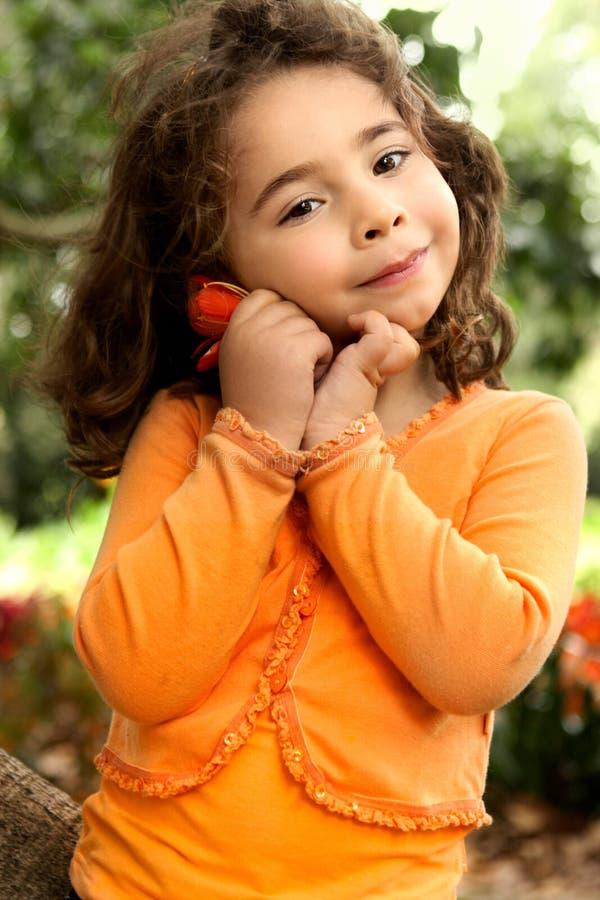 Das schöne kleine Mädchen, das eine Blume hält, wählte vom Garten aus lizenzfreie stockfotos