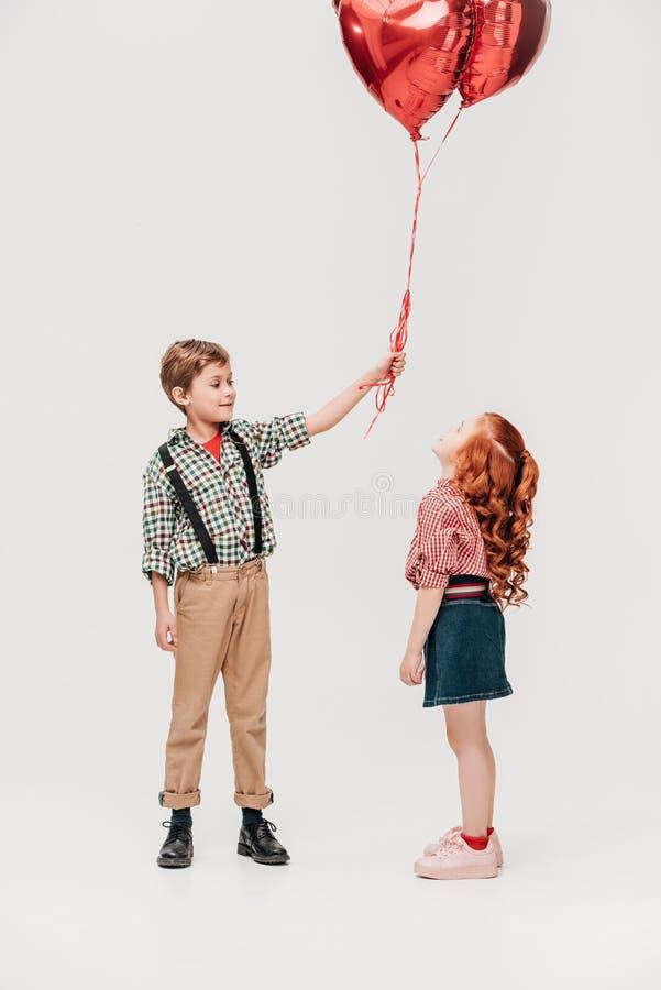 das schöne kleine Mädchen, das den Jungen hält Herz betrachtet, formte Ballone lizenzfreies stockfoto
