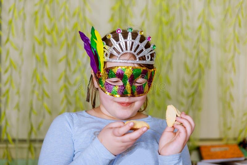 Das schöne kleine Mädchen in den Masken Purim, von glücklichen Menschen in den festlichen Karnevals-Masken feiernd stehen lizenzfreies stockfoto