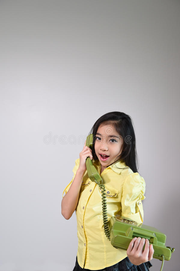Das schöne kleine Mädchen in der Weinleseart sprechend am Telefon stockbilder