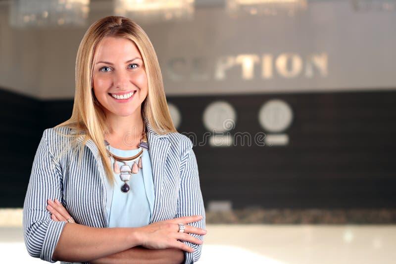 Das schöne lächelnde Geschäftsfrauporträt Lächelnde weibliche Empfangsdame stockfotos