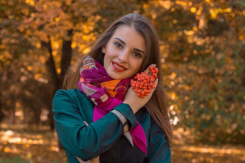 Das schöne lächelnde Mädchen, das auf der Straße steht und hält Ne nahe Gesicht stockfotos