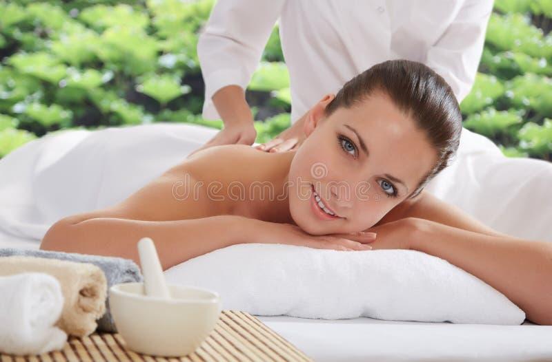 Das schöne Lügen der jungen Frau entspannte sich in einem Badekurortsalon lizenzfreie stockbilder