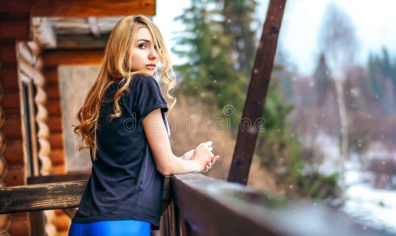 Das schöne Mädchen, das auf dem Portal eines Holzhauses im Winterwald steht und schaut träg zart lizenzfreie stockfotografie