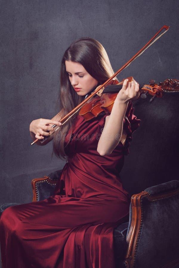 Das schöne Mädchen, das eine Geige mit Augen spielt, schloss stockfotografie