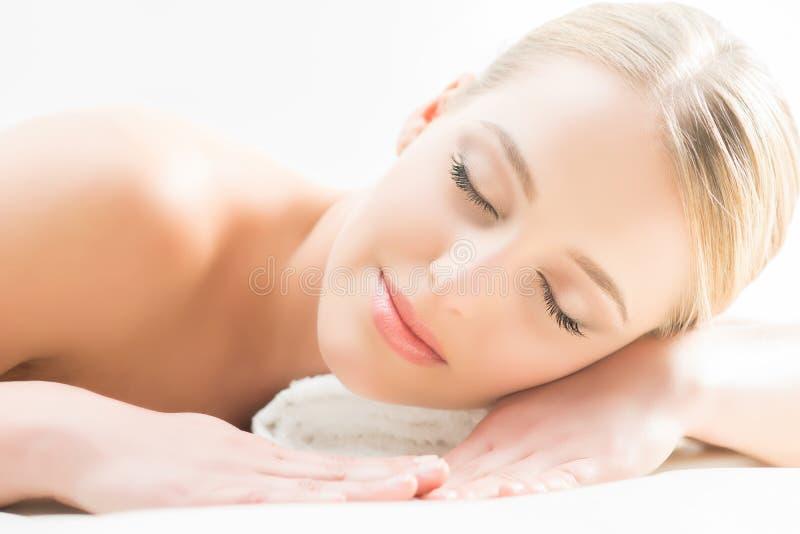 Das schöne Mädchen, das schläft und haben eine Badekur, die auf Weiß lokalisiert wird lizenzfreie stockfotos