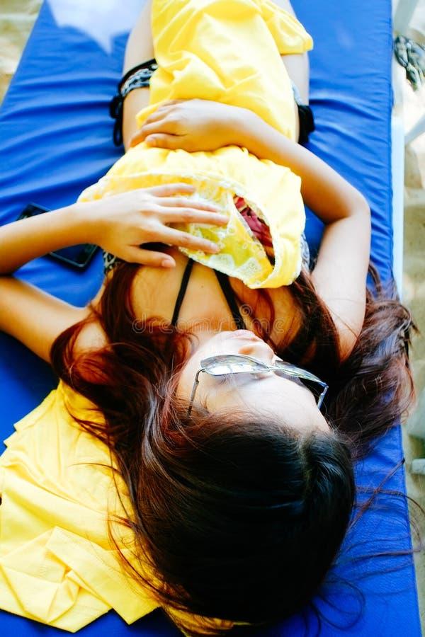 Das schöne Mädchen, das an stillsteht, sunbed während der Ferien auf dem Strand Ein Sonnenbad nehmendes und Entspannungslügen der stockbilder