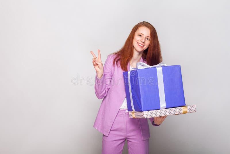 Das schöne Mädchen des Ingwers, das Geschenkkasten hält und haben einen glücklichen Blick a stockfoto