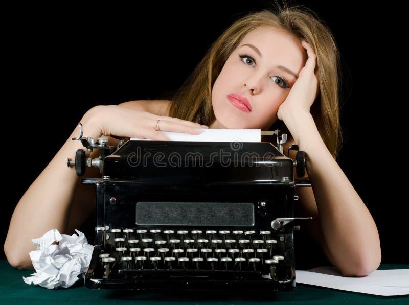 Das schöne Mädchen an einer Schreibmaschine. Eine Retro Art lizenzfreie stockfotografie