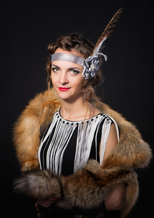 Das schöne Mädchen mit einer Haut des Fuchses auf Schultern und der Feder in der Frisur in Chicago-Art stockfotografie