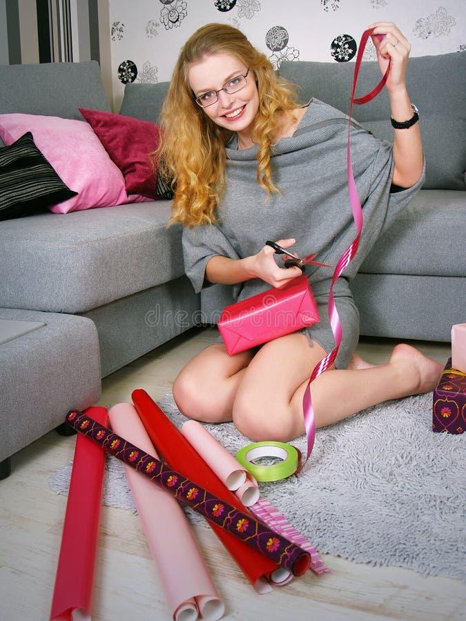 Das schöne Mädchen packt Geschenke für einen Feiertag lizenzfreies stockfoto