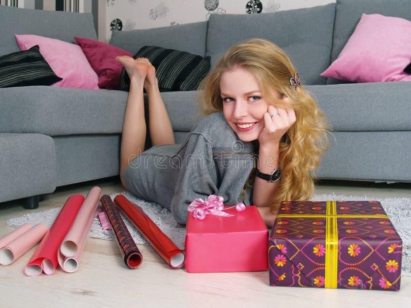 Das schöne Mädchen packt Geschenke für einen Feiertag stockfoto