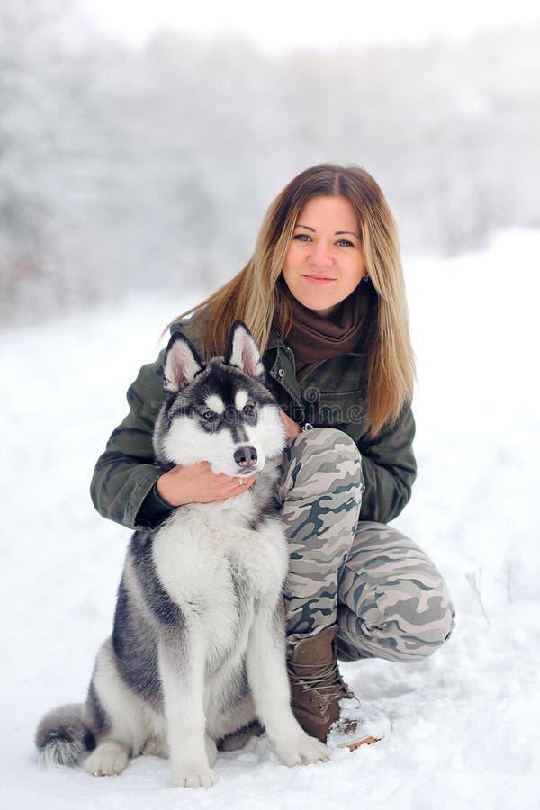 Das schöne Mädchen spielt mit Schlittenhunden eines Welpen lizenzfreies stockbild