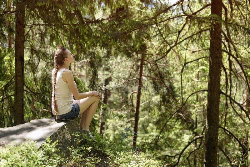 Das schöne Mädchen träumen, das auf einem Stein umgeben durch Koniferenwald an einem sonnigen Tag sitzt stockbilder