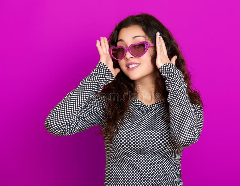 Das schöne Porträt der jungen Frau, aufwerfend auf purpurrotem Hintergrund, langes gelocktes Haar, Sonnenbrille im Herzen formen, stockbilder