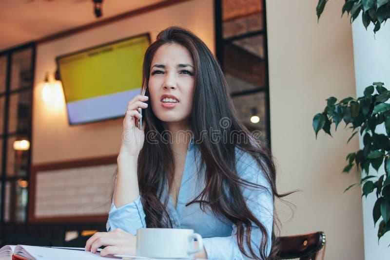 Das schöne reizend brunette verärgerte asiatische Mädchen, das auf Smartphone spricht und pflog ihre Brauen am Café stockfotos