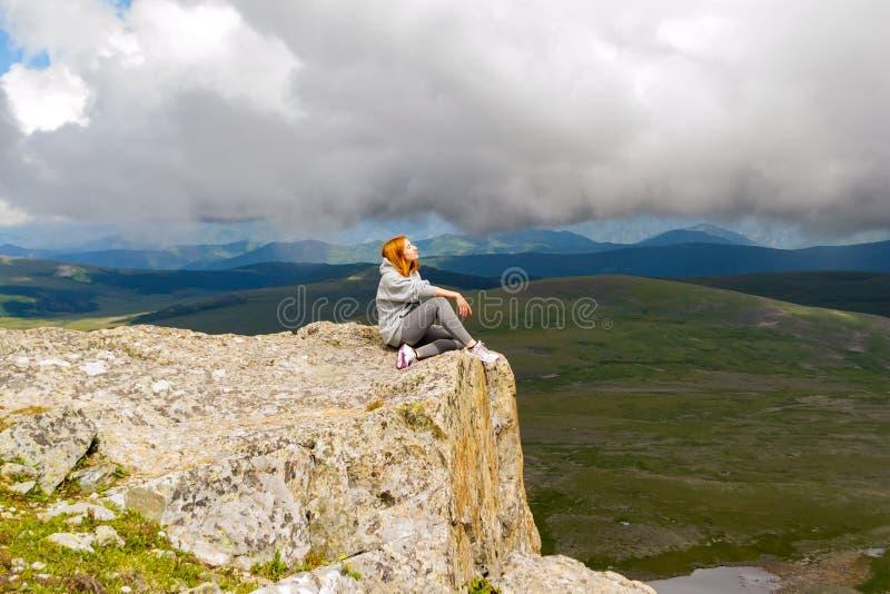 Das schöne rothaarige Mädchen sitzt und entspannend halten Sie ruhiges allein stockbild