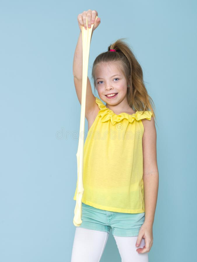 Das schöne und kühle und blonde Mädchen mit 9-jährigen spielt mit gelbem Schlamm vor blauem Hintergrund stockfotos