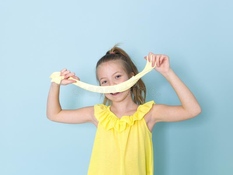 Das schöne und kühle und blonde Mädchen mit 9-jährigen spielt mit gelbem Schlamm vor blauem Hintergrund lizenzfreie stockbilder