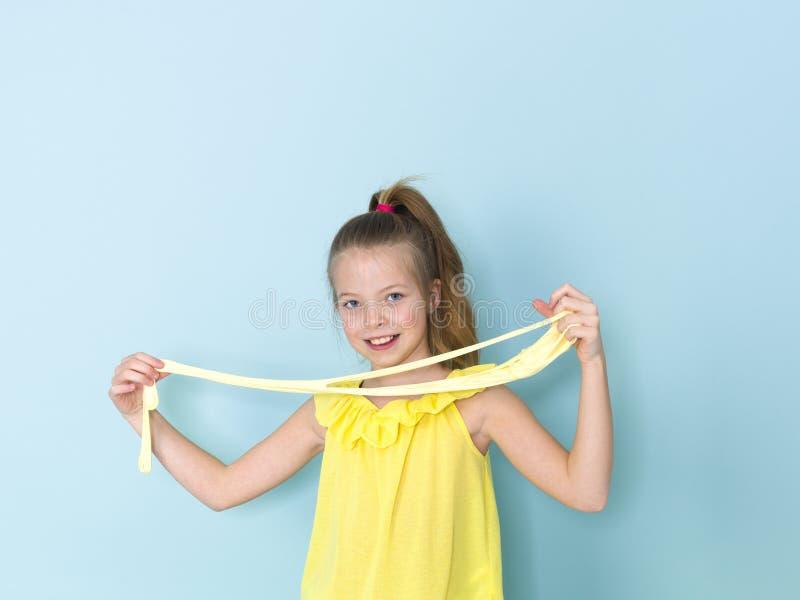 Das schöne und kühle und blonde Mädchen mit 9-jährigen spielt mit gelbem Schlamm vor blauem Hintergrund stockfoto