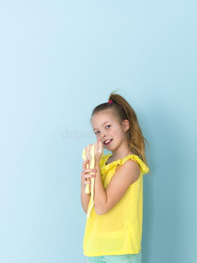 Das schöne und kühle und blonde Mädchen mit 9-jährigen spielt mit gelbem Schlamm vor blauem Hintergrund stockfotografie