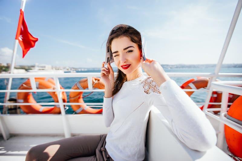 Das schöne vorbildliche Mädchen, das von der Zeitung des hellen Sonnenscheins sitzt auf einer Bootskreuzfahrt sich versteckt, lös stockfotografie