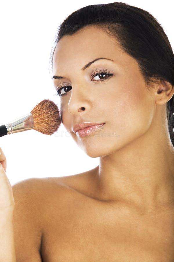 Das schöne Zutreffen der jungen Frau erröten mit Make-upbürste stockbilder