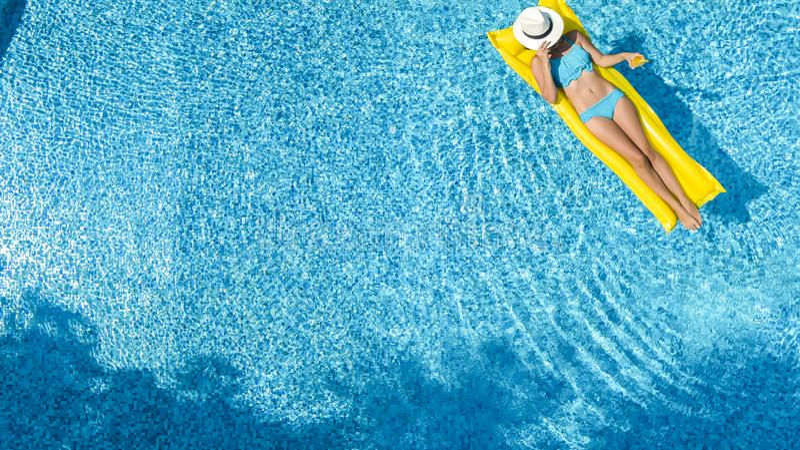 Das sch?ne junge M?dchen, das im Swimmingpool, Schwimmen auf aufblasbarer Matratze sich entspannt und hat Spa? im Wasser auf Fami lizenzfreie stockbilder