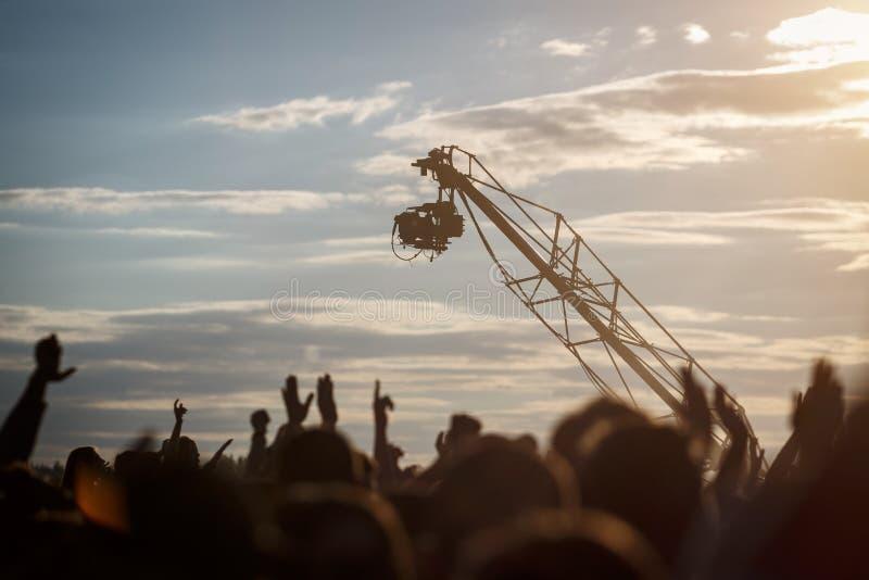 Das Schattenbild der Fernsehkamera hängend am Kran arbeitet an Musikfestival im Freien lizenzfreie stockbilder