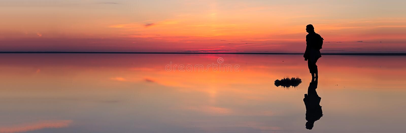 Das Schattenbild des alleinmannes blickend in Richtung des vibrierenden Sonnenuntergangs reflektierte sich im seichten Wasser von stockfotos