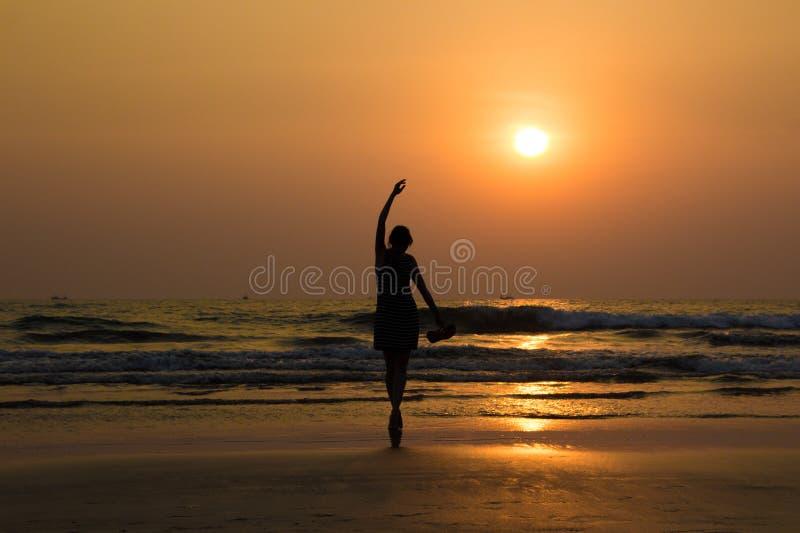 Das Schattenbild des Balletttänzers durch das Meer im Sonnenunterganglicht in Arambol lizenzfreie stockfotografie