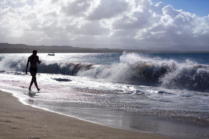 Das Schattenbild des M?dchens gehend entlang den Strand mit Wellen und Wasser spritzt auf Feiertagen, blaues Meer, Wellen sonnen  lizenzfreie stockfotos