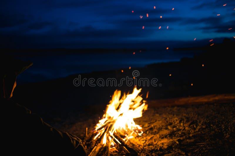 Das Schattenbild des Mädchentouristen um das Lagerfeuer nachts auf dem Flussufer stockbild